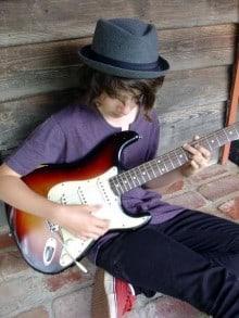 Jaron Natoly playing on the guitar